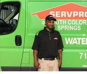 Male employee smiling in front of a green service van