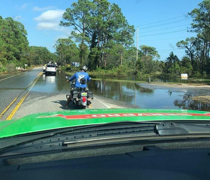 a driver's view in a SERVPRO van, driving near flooded waters