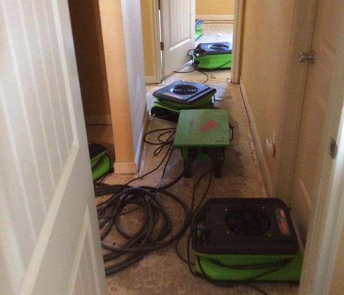 A hallway with the floor torn up, placed with SERVPRO equipment.
