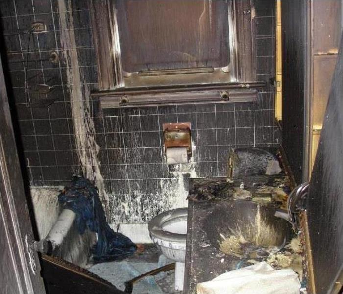 A bathroom covered in soot and smoke damage after a fire