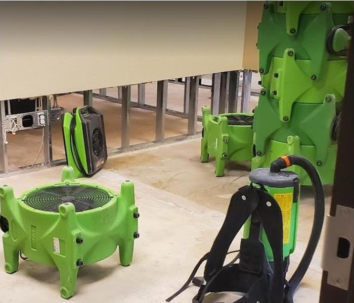 SERVPRO drying equipment being used in water damaged room; flood cuts along walls to enable drying