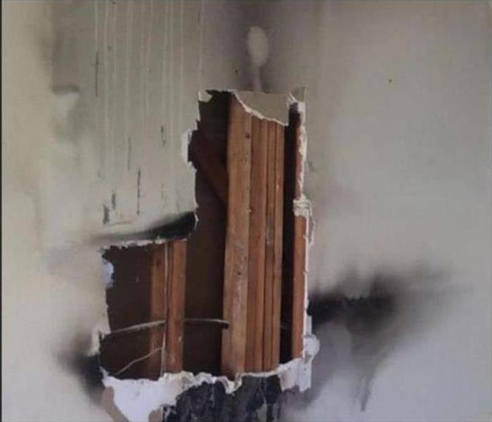 Cavity opened in a drywall, drywall damaged by smoke