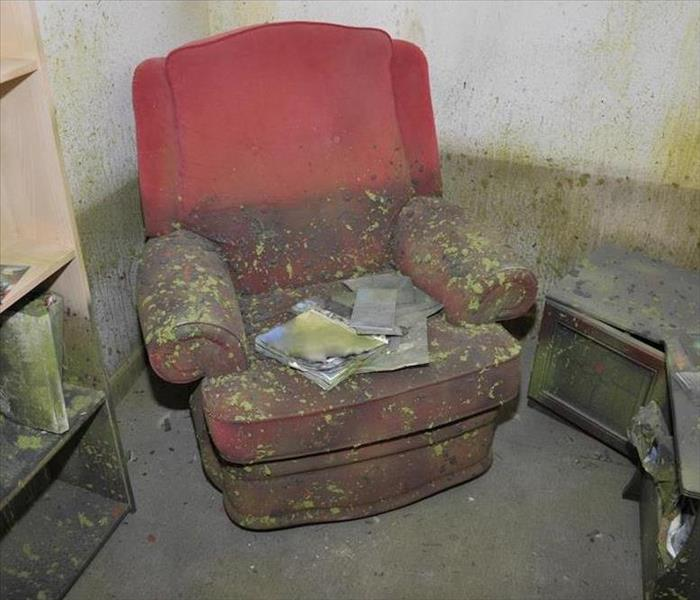 water and mold damaged room with red recliner